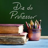 closeup of a chalkboard with the text dia do professor, teachers day written in Portuguese, a pile o poster
