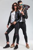 rock and roll man with guitar on shoulder embracing his woman; cool punk couple on grey background poster
