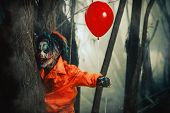 Scary man clown stained in blood in a night forest with a balloon. Male zombie clown. Halloween. Hor poster