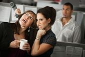 stock photo of strangling  - Frustrated female office worker strangles her coworker with a telephone cord - JPG