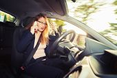 Young female driver talking on cellphone while driving a car poster