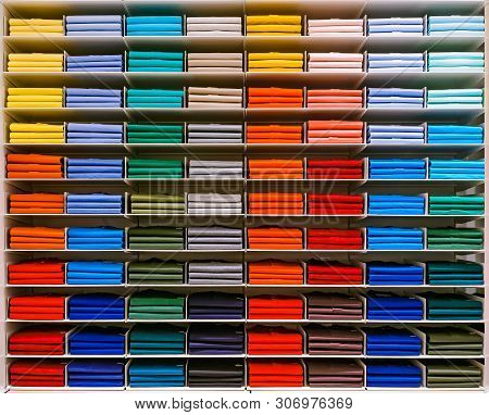 poster of Colorful Rainbow Clothes Background .various Vibrant Color Shirts Perfectly Folded On A Shelf In The