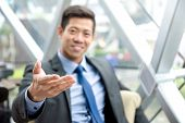 Friendly Asian Businessman Sitting In Office Lounge Reaching Out Hand With Open Palm, Welcome Gestur poster
