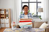 housework, laundry and housekeeping concept - happy african american woman with ironed linen and iro poster