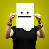 woman holding paper with poker face emoticon against a yellow background