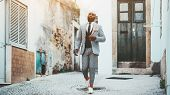 An Elegant Bald Bearded African Man In A Fashion Costume With Tie And Orange Socks Is Walking Down T poster