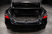 Close Up Rear View Of A  Sedan Black Car With Open Trunk In Garage. Empty Car Trunk poster