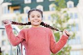 Having Hair In Two Plaits. Adorable Girl Holding Pigtails Hair On Urban Background. Small Cute Girl  poster