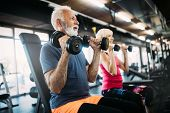 Happy Senior People Doing Exercises In Gym To Stay Fit poster