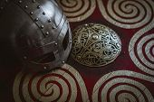 Soldier Viking helmet with chain mail of iron on red shield of wood and golden triskel poster