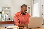 Smiling black man using laptop at home in living room. Happy mature businessman send email and worki poster