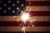Lit sparkler in front the American Flag for 4th of July celebration poster