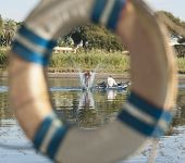 stock photo of nubian  - Traditional local egyptian nubian fishermen fishing in a wooden boat on the river nile abstract view through life ring - JPG