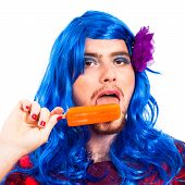 stock photo of transvestite  - Transvestite man in blue wig licking ice pop isolated on white background - JPG