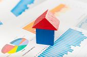 stock photo of depreciation  - Real estate market concept with graphs and house from toy blocks