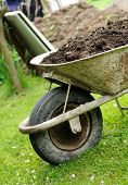 stock photo of hand-barrow  - Hand barrow loaded by earth at the garden - JPG