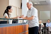 stock photo of receptionist  - Senior man communicating with female receptionist while women sitting in background - JPG