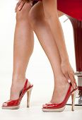 foto of ankle shoes  - Legs and feet of woman wearing sexy high heeled shoes with hand on ankle - JPG