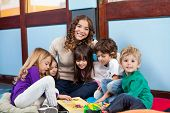 pic of daycare  - Happy teacher sitting with children on floor in classroom - JPG