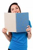 picture of flirtatious  - Flirtatious attractive girl hiding her face behind notebook - JPG