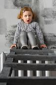 Little girl sitting on a stairs and making angry faces