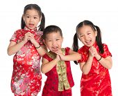 stock photo of little sister  - Little oriental children wishing you a happy Chinese New Year - JPG