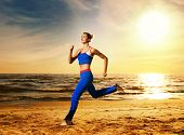 stock photo of athletic woman  - Beautiful young woman running on a beach at sunset