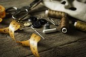 stock photo of tailoring  - Sewing accessories on old wooden table background - JPG