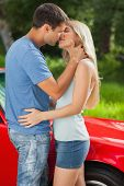 Loving couple kissing passionately by their cabriolet