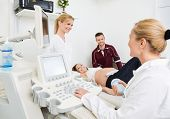 image of gynecologist  - Female gynecologists and expectant couple undergoing ultrasound scan in clinic - JPG