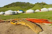 foto of yurt  - Components of a yurt in the foreground and in the background ready yurts - JPG