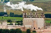 picture of belching  - Four industrial chimneys belching smoke into the atmosphere - JPG