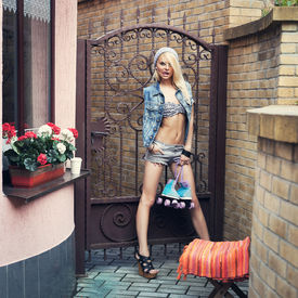 stock photo of roller-derby  - Young pretty blonde woman standing with roller skaters in jeans shirts in the city - JPG