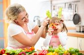 stock photo of apron  - mother and kid cooking and having fun in kitchen - JPG