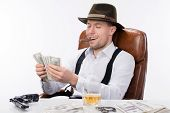 picture of brass knuckles  - gangster sitting at a table counting money - JPG