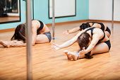 pic of pole dancing  - Group of young women stretching and warming up on the floor for their pole dancing class - JPG