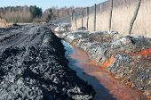 stock photo of sewage  - Polluted water and waste heap (coal mine industry)