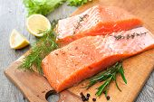 foto of slating  - Raw salmon fish fillet with fresh herbs on cutting board