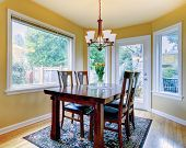 pic of small-flower  - Yellow wall small dining room with hardwood floor and rug - JPG