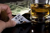 picture of splayed  - poker  cards dollars and a whiskey glass - JPG