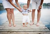stock photo of baby feet  - Closeup of feet of family with little baby boy walking on pier - JPG