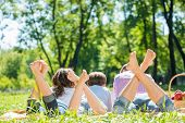stock photo of barefoot  - Young happy family lying in park barefoot - JPG