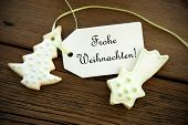 stock photo of weihnachten  - The German Words Frohe Weihnachten which means Merry Christmas on a Label with Cookies - JPG