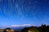stock photo of nepali  - Star trails over Bandipur village and the Himalayas - JPG