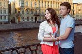 stock photo of attention  - Young couple emracing and look left with hope and attention - JPG