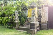 picture of garden sculpture  - Bali Temple with Three Statues On Lush Green Garden - JPG