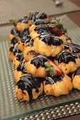 picture of eclairs  - Eclair with hot chocolate fudge on food table - JPG