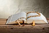stock photo of rosary  - rosary with old bible on the desk - JPG