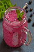 stock photo of mason  - Blueberry smoothie in a mason jar with a straw and sprig of mint - JPG