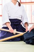 stock photo of aikido  - Man and woman fighting with wooden swords at Aikido training in martial arts school  - JPG